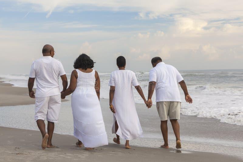 Den lyckliga höga afrikanska amerikanen kopplar ihop mankvinnor på stranden royaltyfria foton
