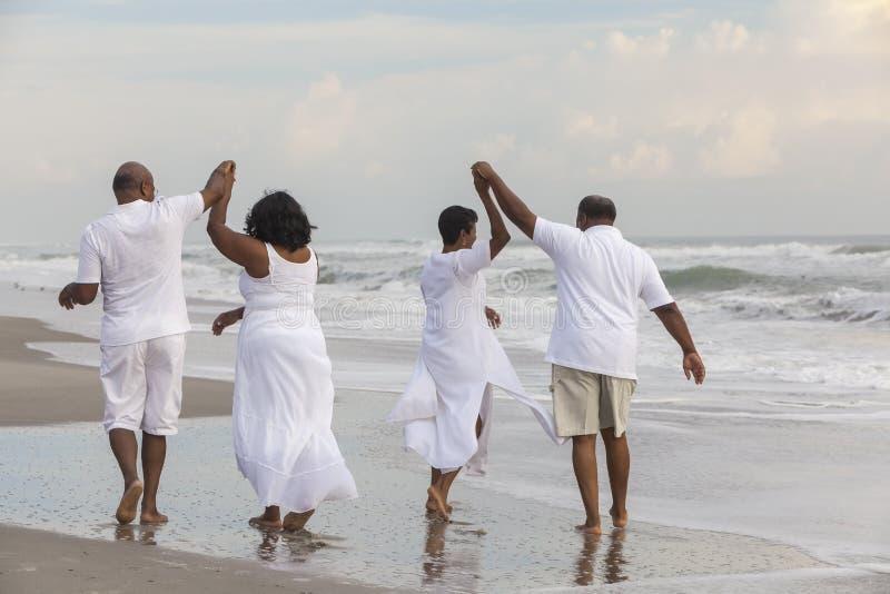 Den lyckliga höga afrikanska amerikanen kopplar ihop mankvinnor på stranden royaltyfri foto