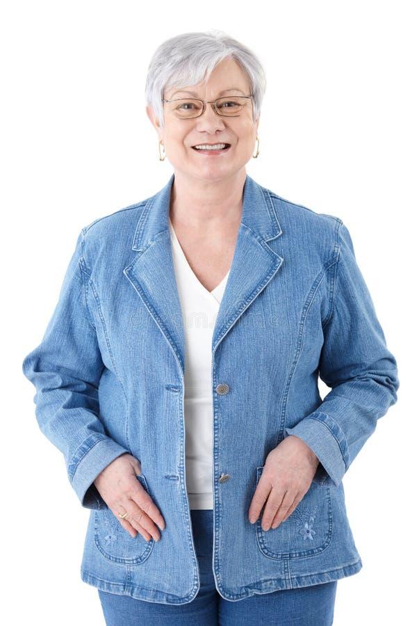 Den lyckliga höga kvinnan i denim klår upp att le royaltyfria foton