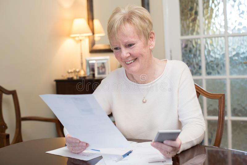 Den lyckliga höga kvinnan som granskar hemhjälp, finansierar hemma royaltyfri fotografi