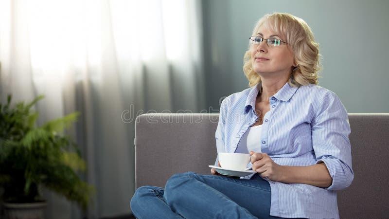 Den lyckliga höga kvinnan som sitter på soffan med kopp te, hälsa och avgång, vilar arkivbild