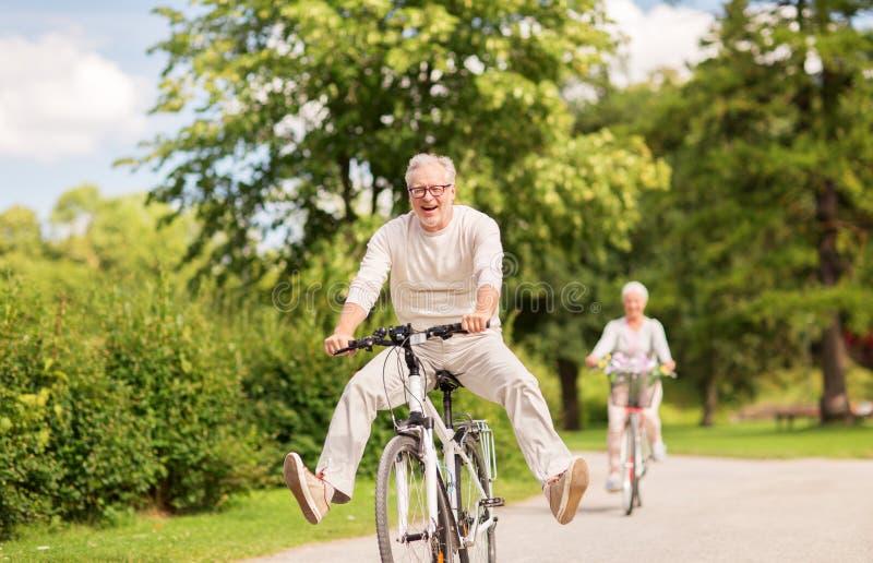 Den lyckliga höga parridningen cyklar på sommar parkerar royaltyfri fotografi
