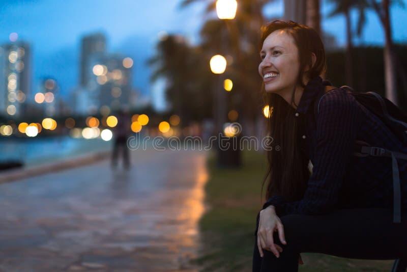 Den lyckliga högskolestudentkvinnan som tycker om staden, parkerar royaltyfri foto