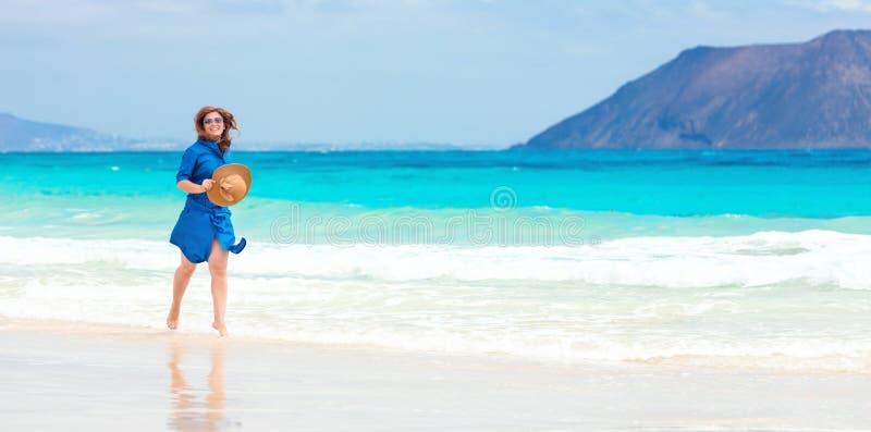Den lyckliga handelsresandekvinnan i blå klänning tycker om hennes tropiska strandsemester arkivfoto
