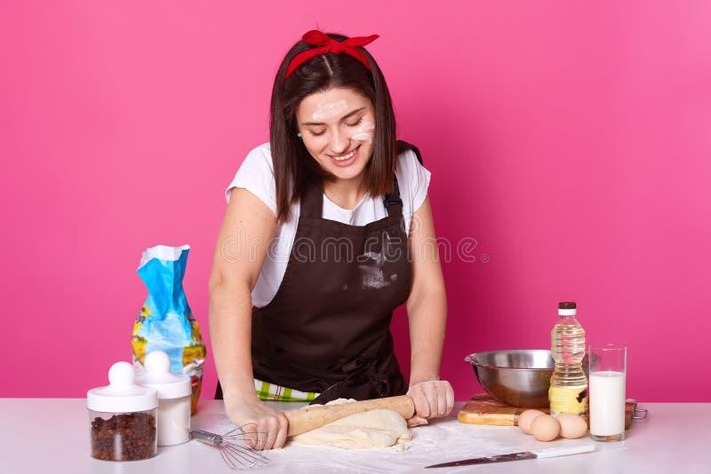 Den lyckliga hemmafrun eller bagaren rymmer att baka kavlen och rullar ut deg med tyckt om ansiktsuttryck Studiobild ?ver arkivfoton