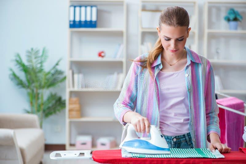 Den lyckliga hemmafrun som gör att stryka hemma royaltyfri bild