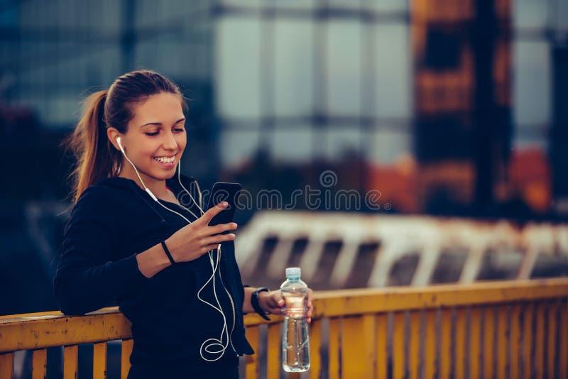 Den lyckliga idrotts- flickan som tar ett avbrott efter, utarbetar och lyssnande musik, medan genom att använda den smarta telefo royaltyfri bild