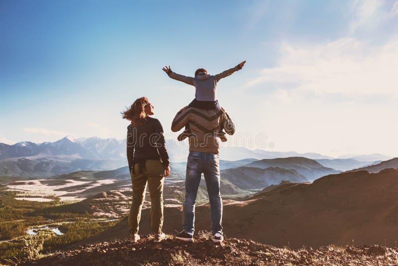 Den lyckliga idylliska familjen mot berg har gyckel arkivbilder