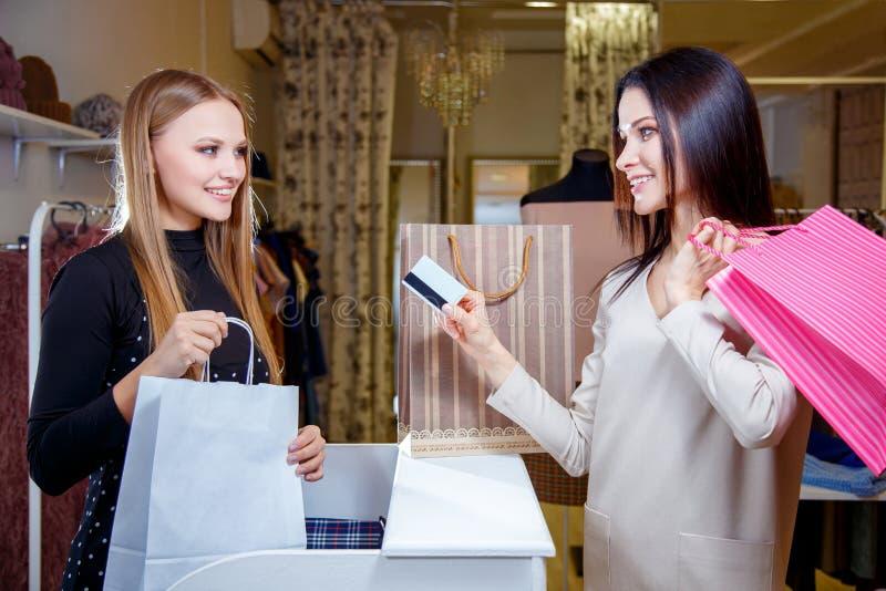 Den lyckliga kvinnakunden som betalar med kreditkorten i mode, shoppar royaltyfri fotografi