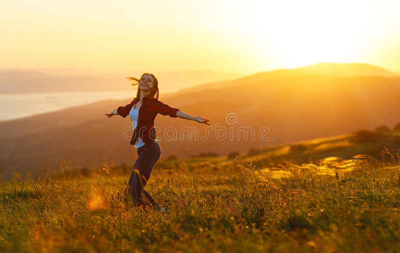 Den lyckliga kvinnan dansar, jublar, skrattar på solnedgång i natur arkivbilder