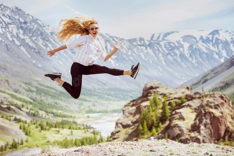 Den lyckliga kvinnan hoppar berglopp fotografering för bildbyråer