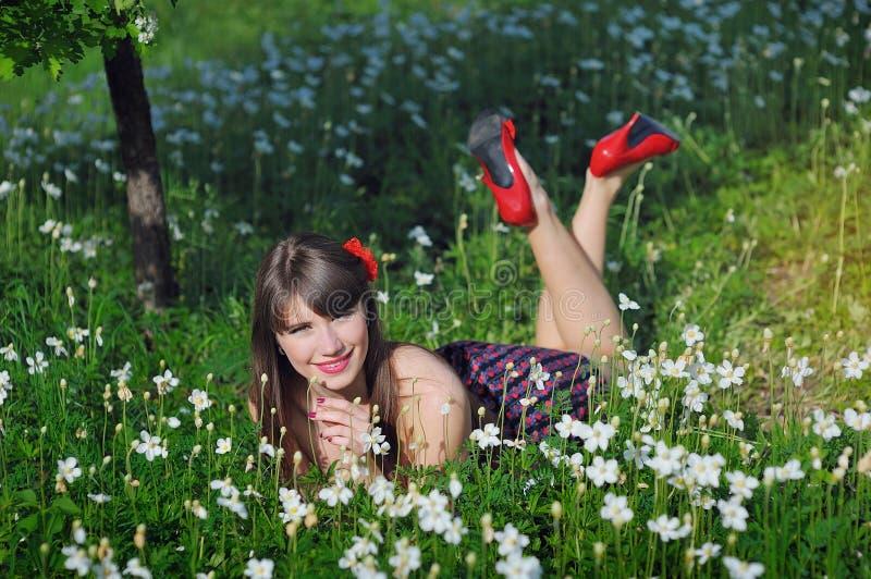 Den lyckliga kvinnan i en vårträdgård är i färg, med röda skor arkivbild