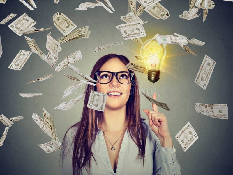Den lyckliga kvinnan i exponeringsglas har en lyckad idé under pengarregn royaltyfri bild