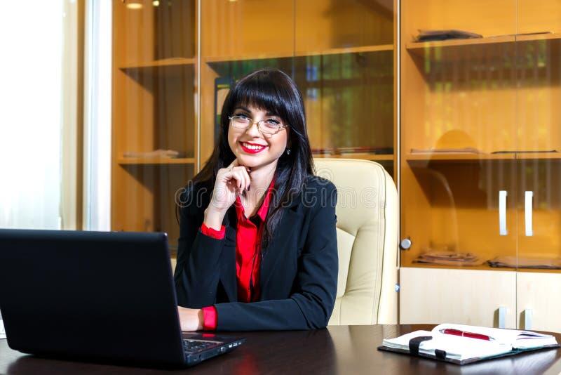 Den lyckliga kvinnan i exponeringsglas sitter på en tabell i kontoret royaltyfria foton