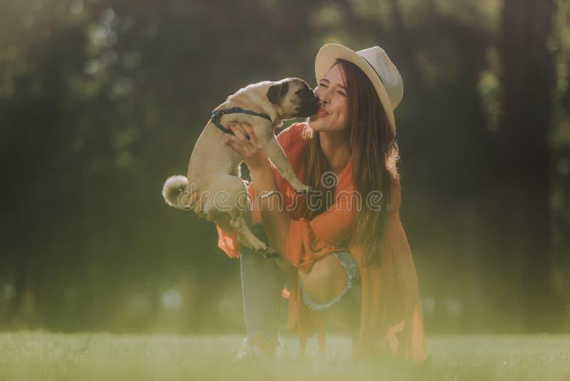 Den lyckliga kvinnan i hatt kysser hennes valp arkivfoto
