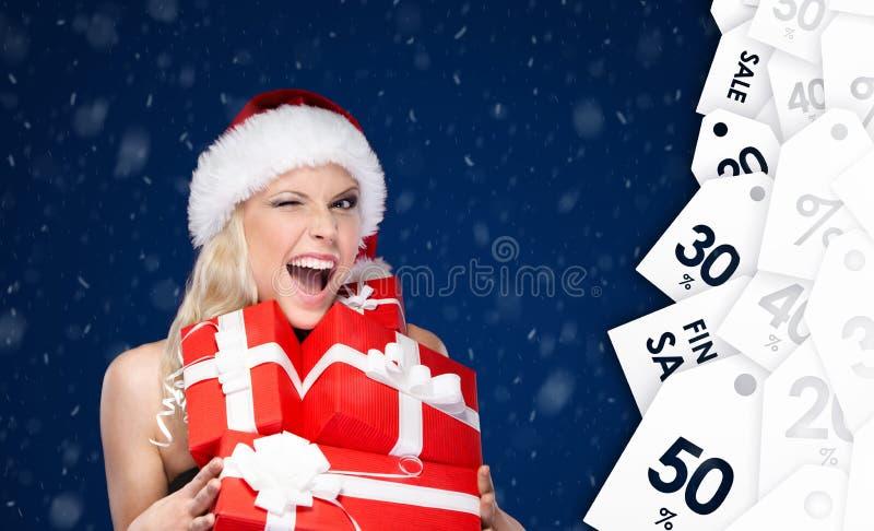 Den lyckliga kvinnan i jullock rymmer en uppsättning av gåvor royaltyfri fotografi