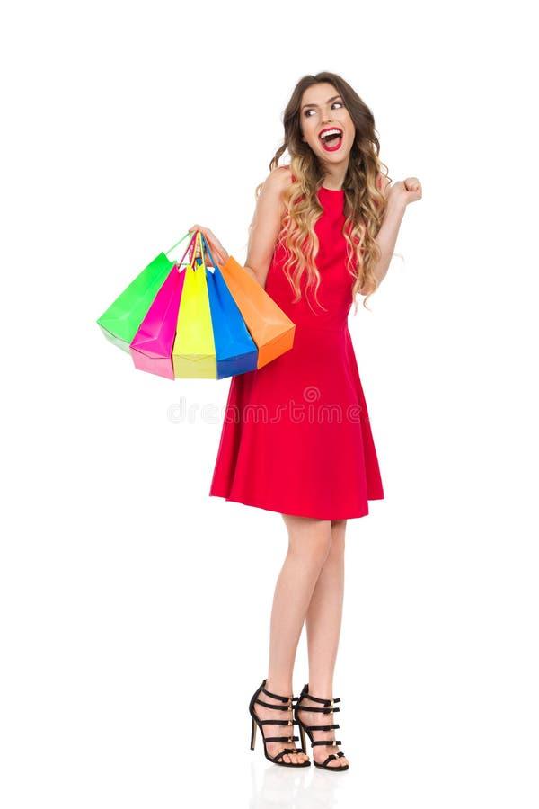 Den lyckliga kvinnan i röd klänning med färgrika shoppingpåsar är ropa och se bort royaltyfria bilder