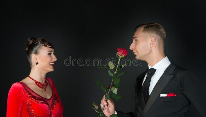 Den lyckliga kvinnan i röd klänning och mannen med rosen blommar royaltyfri bild