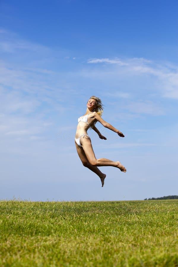 Den lyckliga kvinnan i vita bikinihopp i ett sommargräsplanfält mot den blåa himlen royaltyfri fotografi