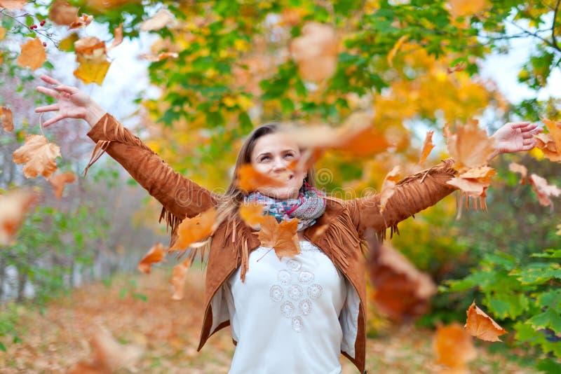 Den lyckliga kvinnan kastar leaves arkivbilder