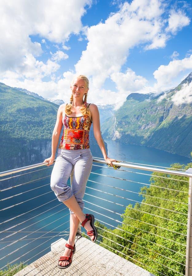 Den lyckliga kvinnan kopplar av på den Geiranger fjorden Flickan tycker om bra väder i Norge royaltyfria foton