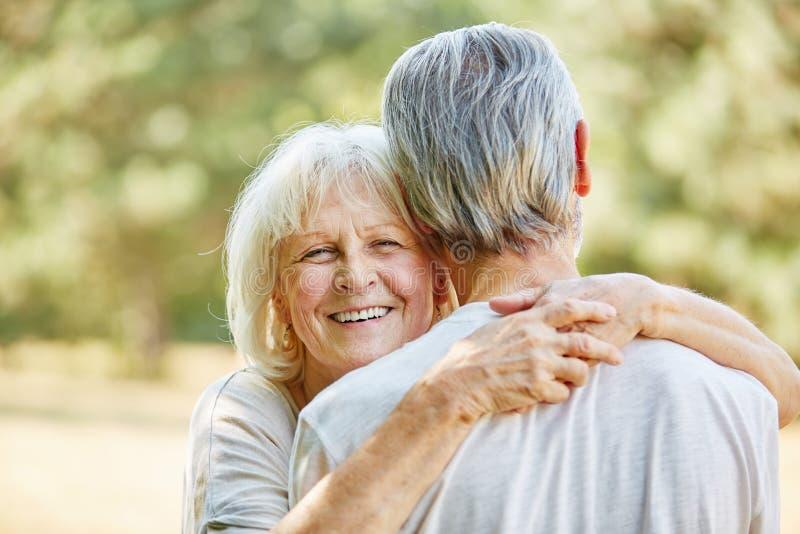 Den lyckliga kvinnan kramar en man fotografering för bildbyråer
