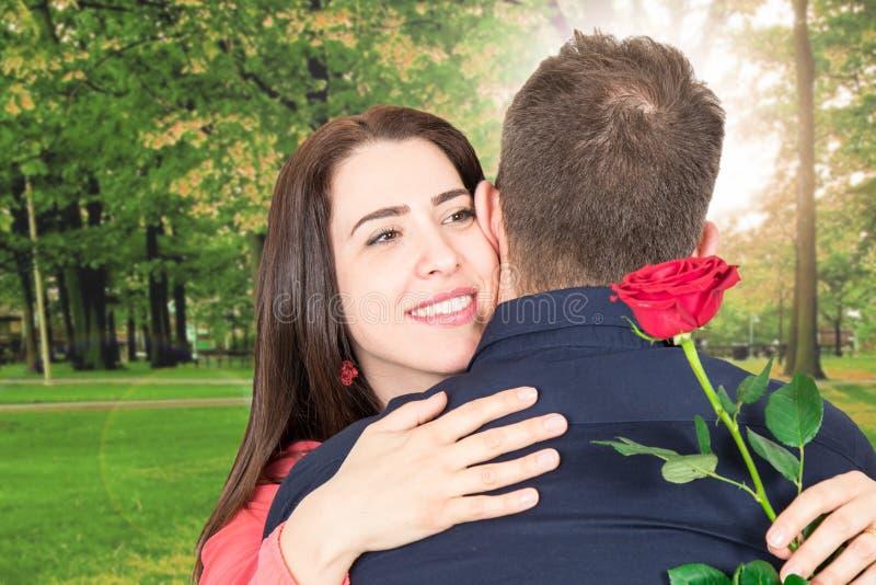 Den lyckliga kvinnan kramar hennes förälskelse som rymmer en ros i en parkera arkivfoton
