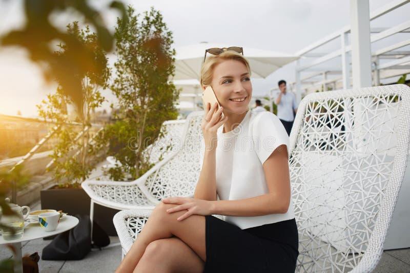 Den lyckliga kvinnan ler foen någon, medan talar på celltelefonen under vilar i kafé arkivbild