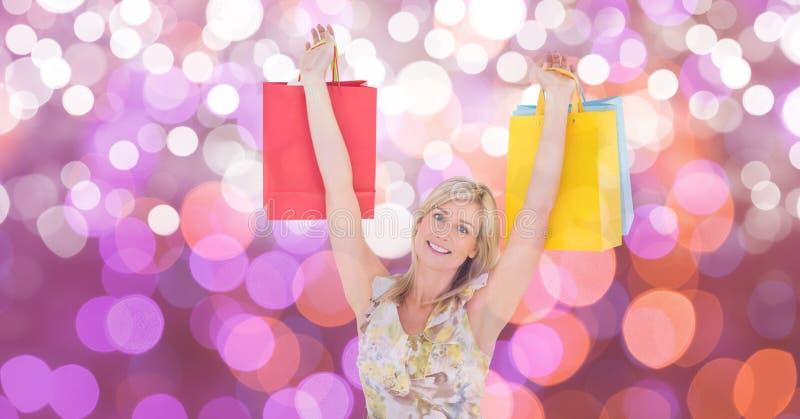 Den lyckliga kvinnan med armar lyftte bärande shoppingpåsar över bokeh arkivfoton