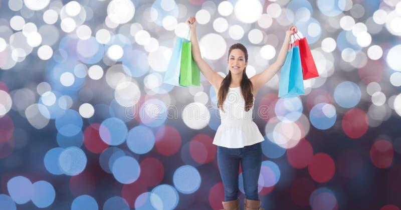 Den lyckliga kvinnan med armar lyftte hållande shoppingpåsar över bokeh arkivbilder