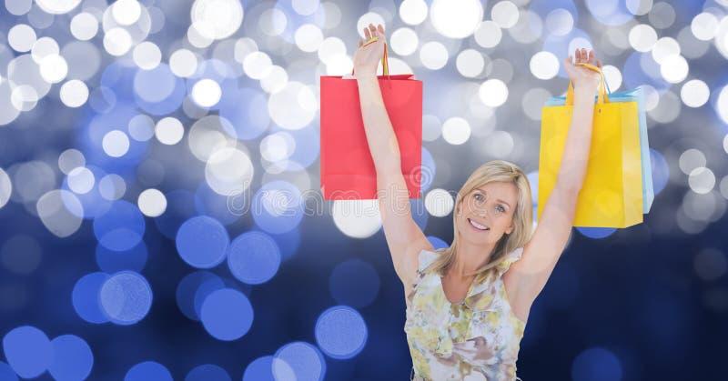 Den lyckliga kvinnan med armar lyftte hållande shoppingpåsar royaltyfri bild