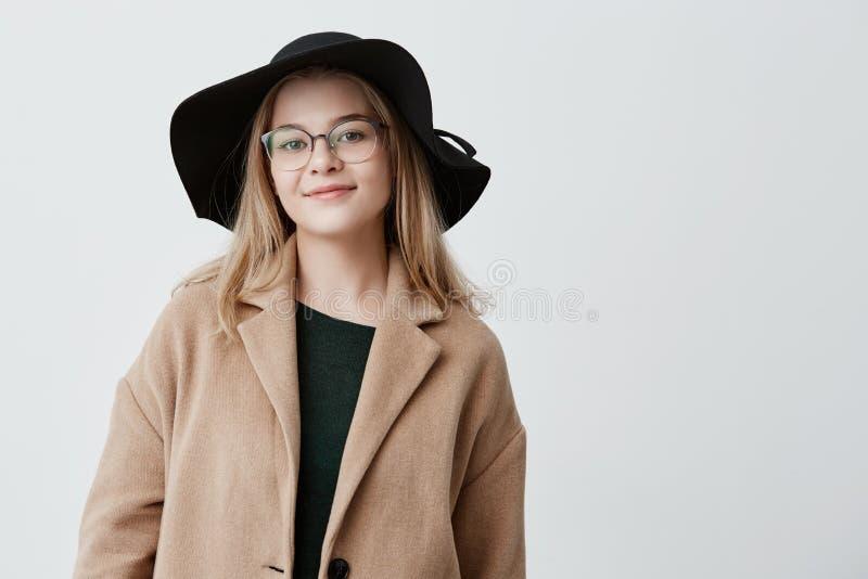 Den lyckliga kvinnan med attraktivt utseende, det iklädda moderiktiga laget och den svarta hatten, med glasögon på, uttrycker rea royaltyfria foton