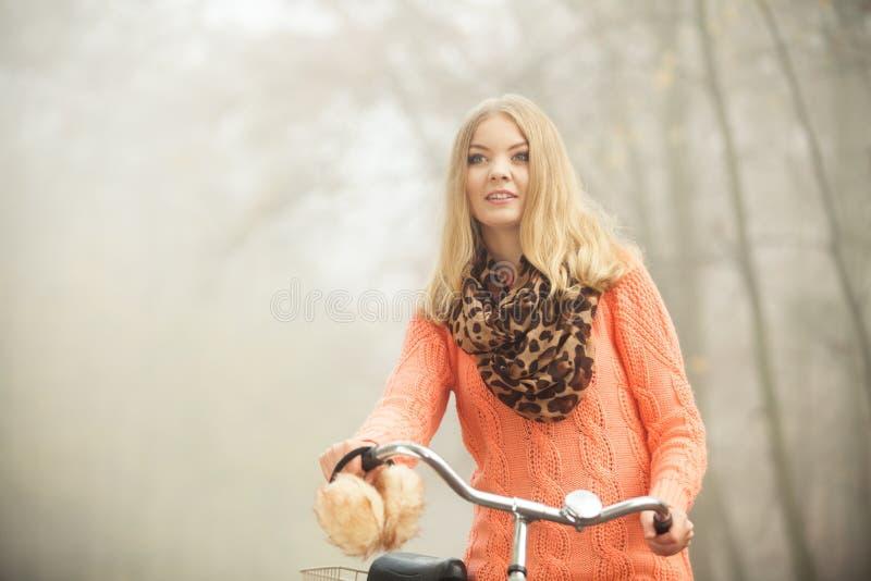 Den lyckliga kvinnan med cykelcykeln i höst parkerar royaltyfria foton