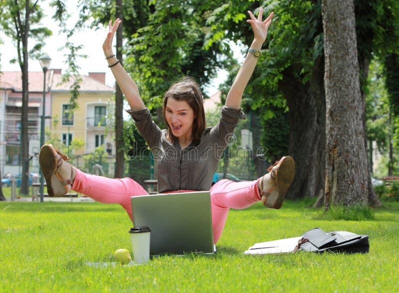 Den lyckliga kvinnan med datoren i en Urban parkerar royaltyfri bild