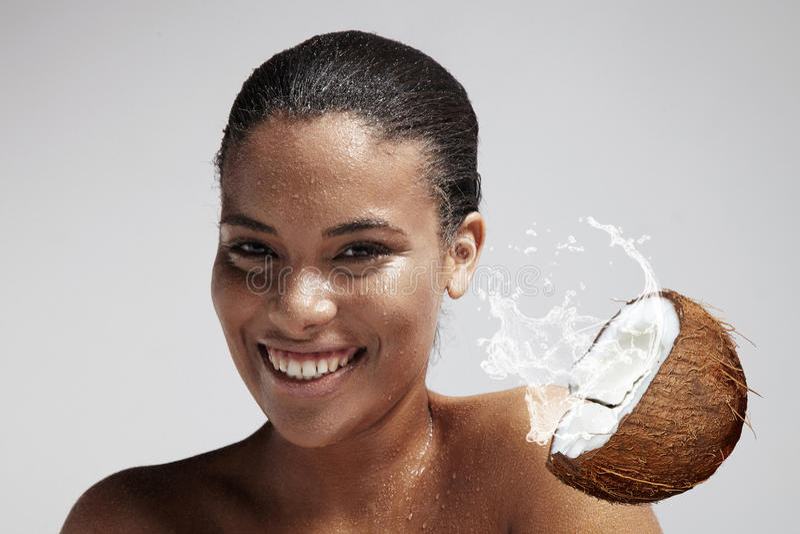 Den lyckliga kvinnan med droppar av en kokosnöt mjölkar på hennes hud royaltyfria foton
