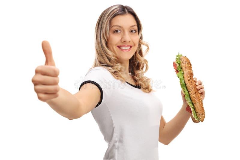 Den lyckliga kvinnan med en smörgås som gör en tumme gör en gest upp royaltyfri foto