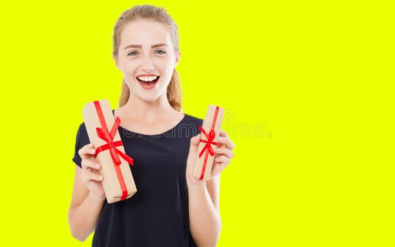 Den lyckliga kvinnan med gåvaaskar som isoleras på gul bakgrund, jul semestrar begrepp arkivfoto