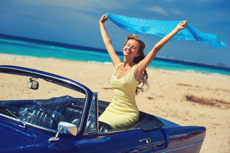 Den lyckliga kvinnan med händer lyftte sammanträde i retro bil royaltyfria foton