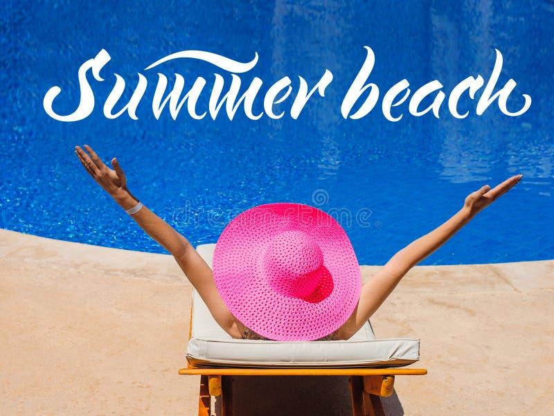 Den lyckliga kvinnan med hatten som solbadar på en soldagdrivare vid pölen, och ordsommar sätter på land arkivfoton