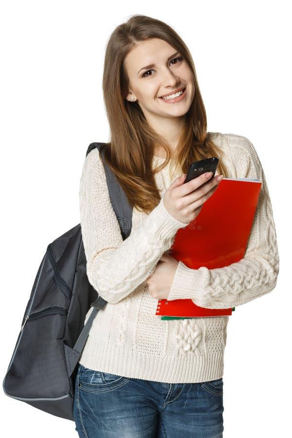 Den lyckliga kvinnan med ryggsäck och bokar med cellen ringer arkivbild