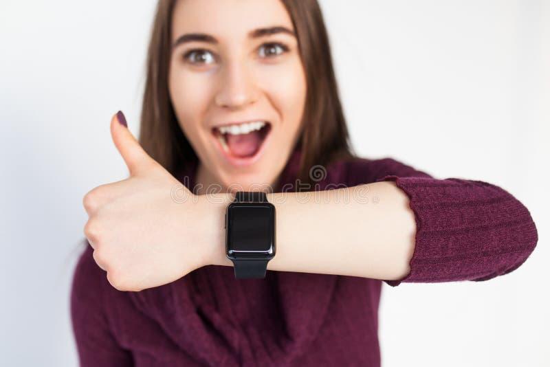 Den lyckliga kvinnan med smart klockavisning tummar upp royaltyfri fotografi