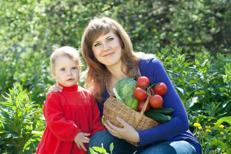 Den lyckliga kvinnan och behandla som ett barn flickan med grönsaker fotografering för bildbyråer