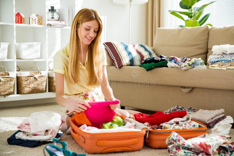 Den lyckliga kvinnan packar försiktigt kläder in i resväskan royaltyfri foto