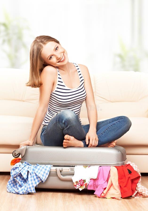 Den lyckliga kvinnan packar resväskan hemma royaltyfria bilder