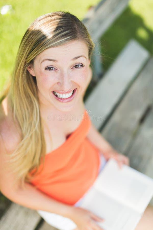 Den lyckliga kvinnan parkerar på bänken arkivfoto