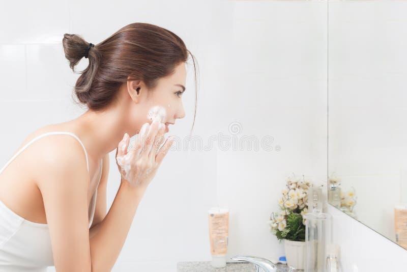 Den lyckliga kvinnan rentvår huden med skum i badrum royaltyfria foton