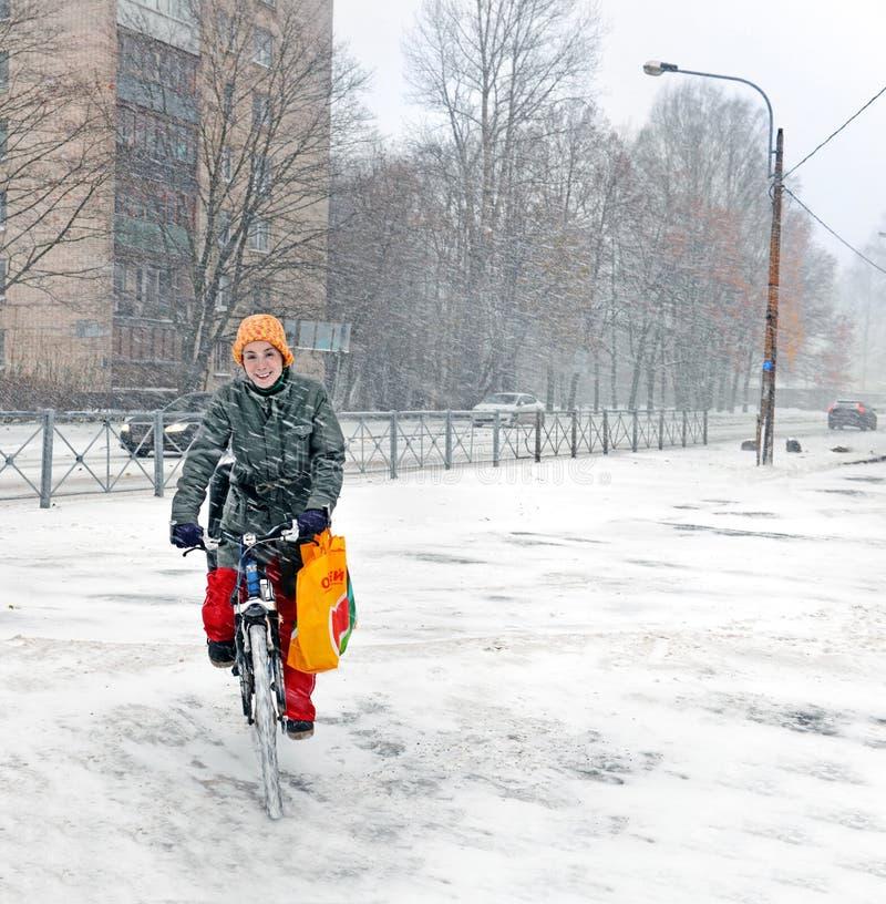 Den lyckliga kvinnan rider en cykel i vinterstaden arkivfoton