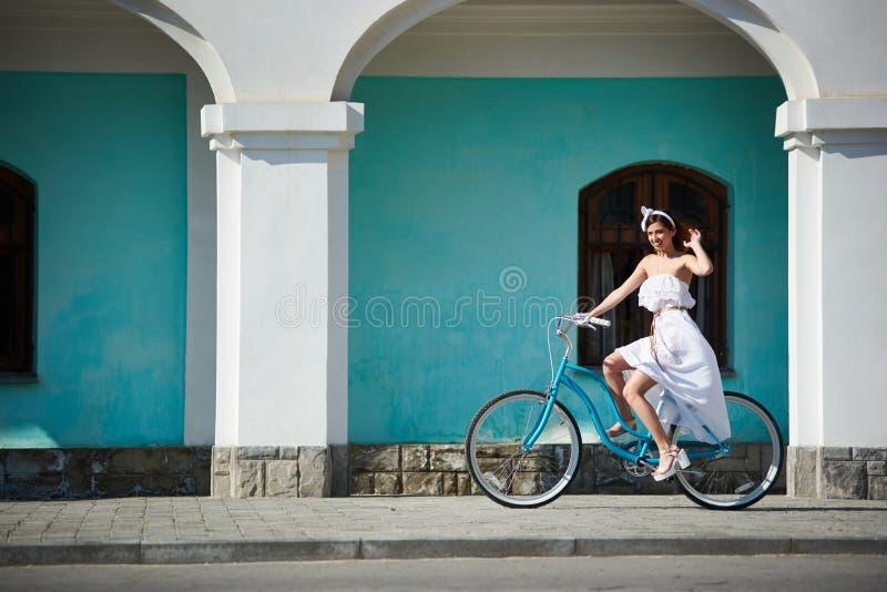 Den lyckliga kvinnan rider den retro cykeln i varm sommardag royaltyfri fotografi