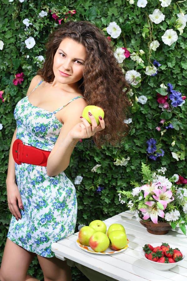 Den lyckliga kvinnan rymmer äpplet och står den nästa tabellen med äpplen arkivfoton