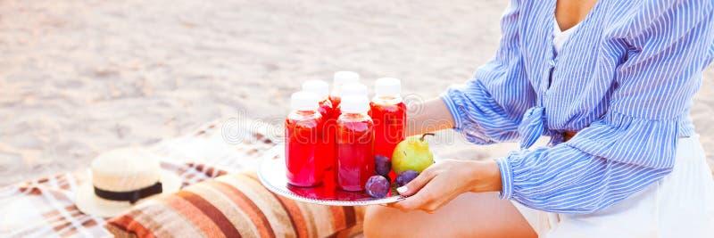 Den lyckliga kvinnan rymmer en maträtt med en röd fruktsaft för drinkar på solnedgången Picn royaltyfri foto